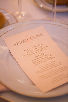 Wedding reception menu with golden and pink font on white china with gold rims