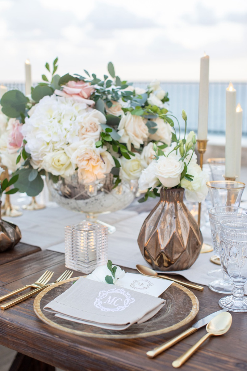 wedding reception wood table gold flatware charger white hydrangea pink rose bronze vase crystal