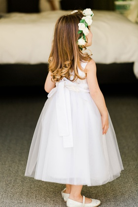 flower girl in white dress bow in back flats curled hair white rose greenery flower crown halo