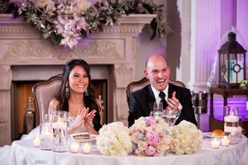 Bride with chandelier earrings & groom in a black tuxedo, sit at sweetheart table with white roses