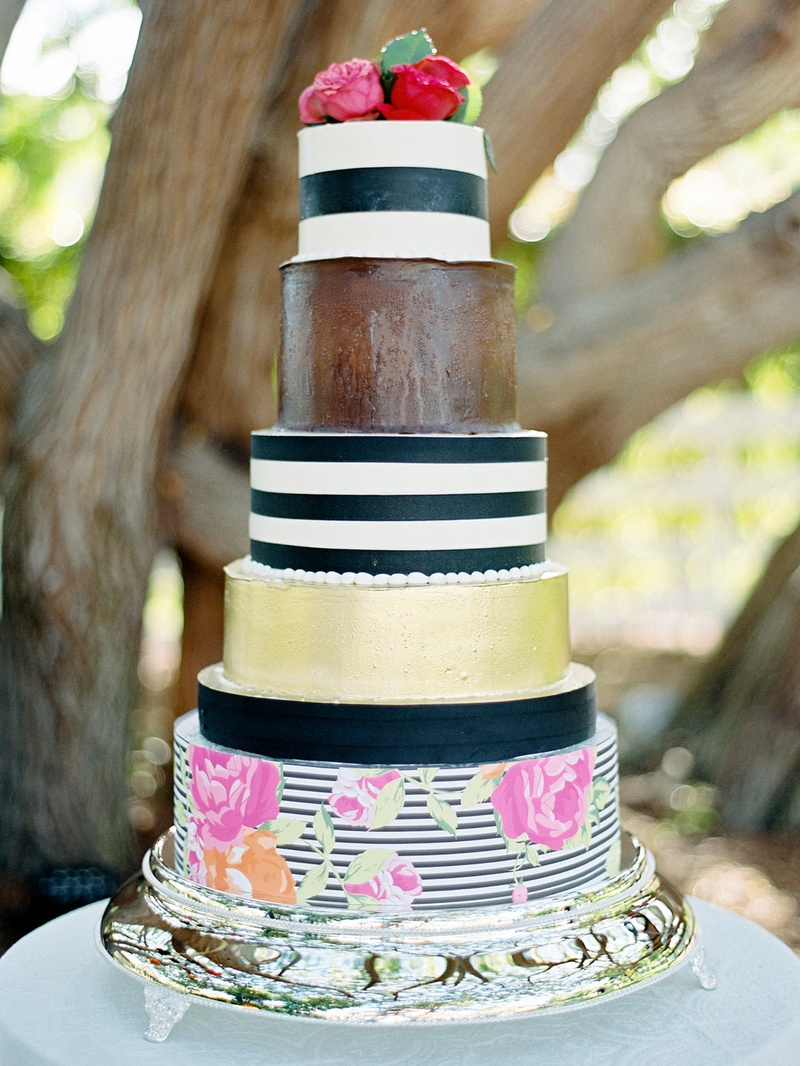 Whimsical wedding cake with black and white stripes, gold, and flower print decorations