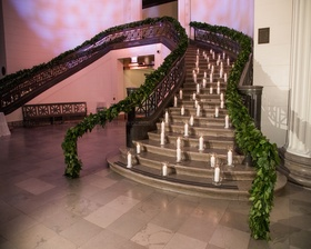 Beautiful green garland on a brightly lit staircase.