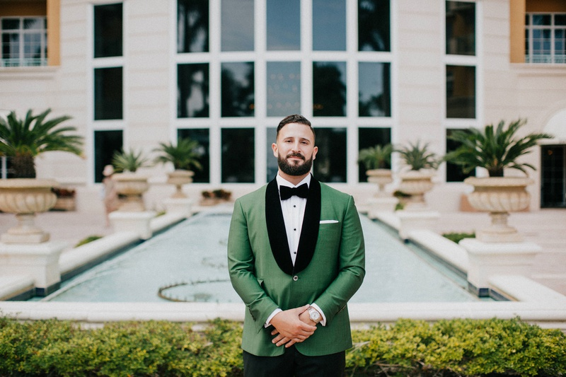 wedding in miami florida groom waiting for first look green tux jacket black velvet lapels pocket