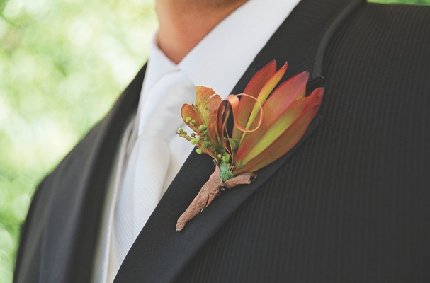 Groom wearing orange flowers on lapel