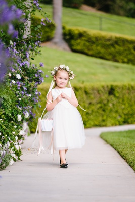 adorable flower girl with flower crown, basket in crook of arm, black shoes