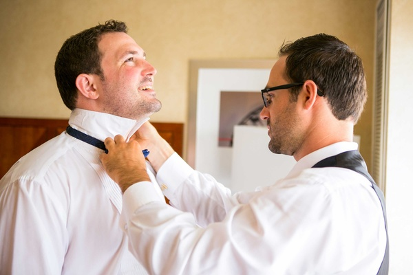 best man helps groom tie bow tie