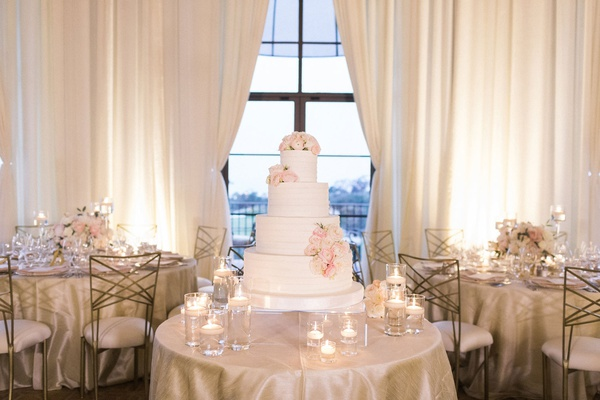 wedding cake white four layer confection fresh flowers pink white blooms floating candles