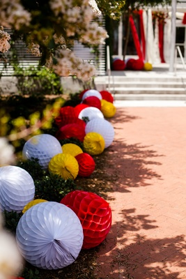 Fanned paper lanterns on ground leading to reception