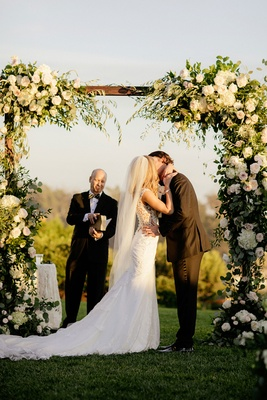 Amy Crawford and Gerrit Cole white veil under arbor with greenery and white flowers gerrit cole