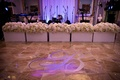 Custom dance floor with silver B monogram and flower boxes with hydrangea, rose, orchid next to band