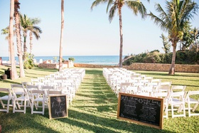 a ceremony space on lawn in front of pacific ocean with chalkboard programs