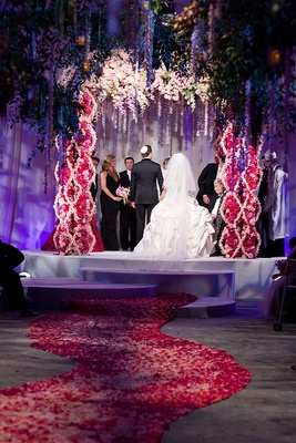 Bride and groom under flower chuppah at indoor garden ceremony