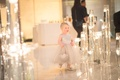 Little girl walking by floating candles in silver shoes