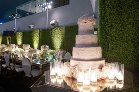 Outdoor rooftop wedding white wedding cake round layers fresh peony flowers on top and base candles