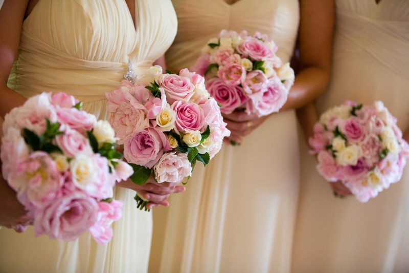 Pale yellow dresses and bright rose nosegays