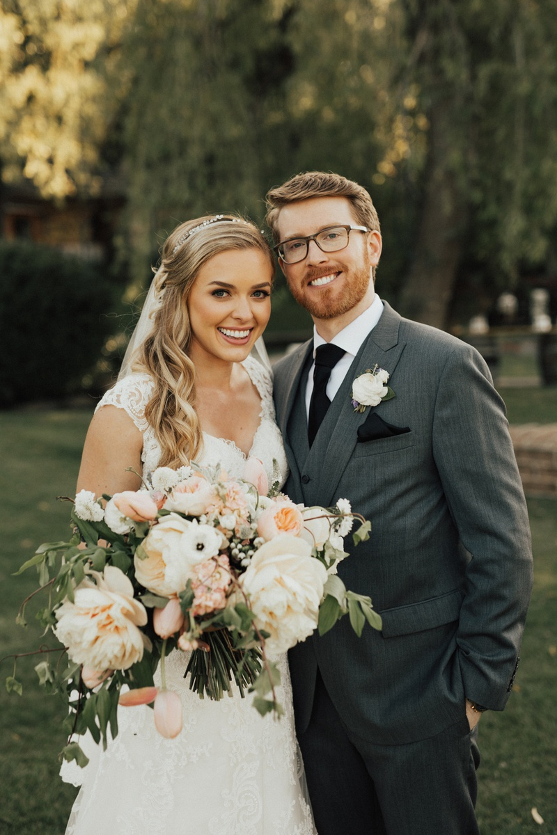 blonde bride in lace stella york gown with groom in three-piece grey suit and black tie.