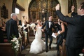 bride in ruffled vera wang gown with groom in tux holding hands during recessional in catholic chuch