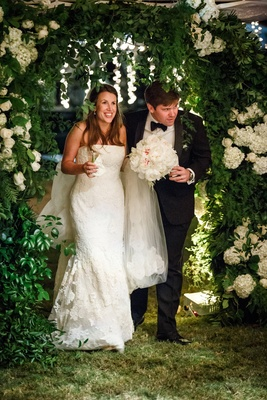 bride in vera wang, groom in tuxedo walk through arch of greenery and white flowers enter reception