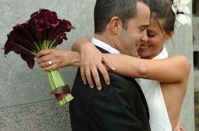 Bride hugs groom with burgundy calla lilies