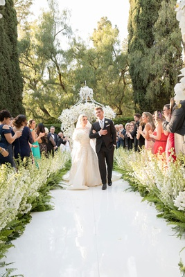 Beverly HIlls Hotel wedding bride and groom walking up aisle stock and ferns along aisle white arch
