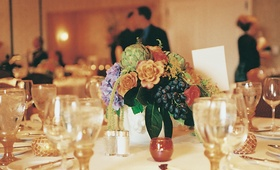 Flower centerpiece with artichokes and grapes