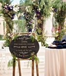 chalkboard ceremony sign on easel with greenery accents
