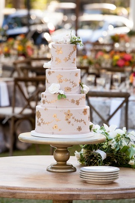 Wedding cake with four tiers rose gold flower details and blush fondant decorations white flowers