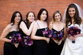 bridesmaids wearing black spaghetti strap dresses and holding purple and pink bouquets
