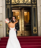 Woman in wedding dress kissing man in front of The Plaza Hotel