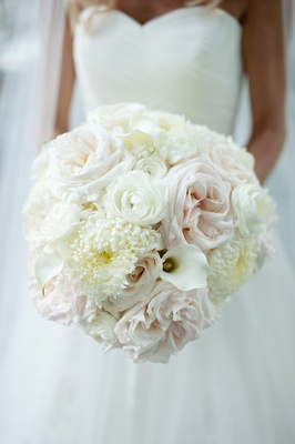 White winter wedding bouquet with ranunculus, calla lily, rose, and crysanthemum flowers