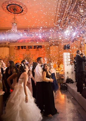 wedding guests including the bride watch the stage as confetti falls during ceremony