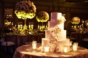 Four layer wedding cake ivory frosting fresh flowers on each layer candles on cake table