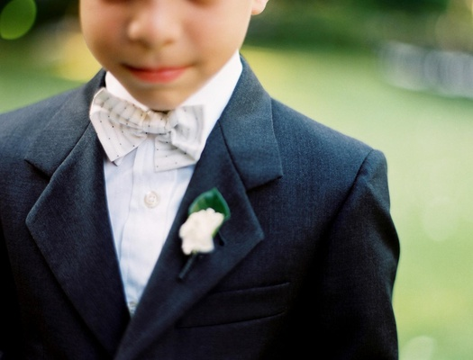 Ring bearer in a dark suit and light bow tie