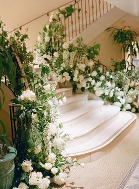 stairs to wedding reception ballroom decorated with fresh greenery and white flowers dahlias roses