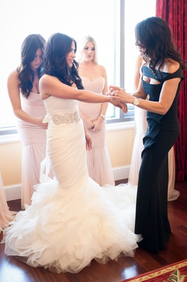 bride in vera wang, bridesmaids in amsale, bride's mother and sisters help her get ready