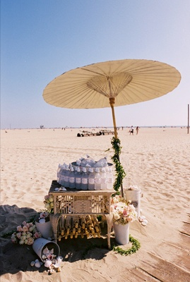 Personalized bottled water and parasols for beach wedding