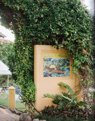 Wedding rehearsal dinner Mexico location venue with tile sign grass lawn hedge wall