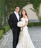 Bride in off the shoulder Pnina Tornai wedding dress and groom in tuxedo with white bow tie glasses