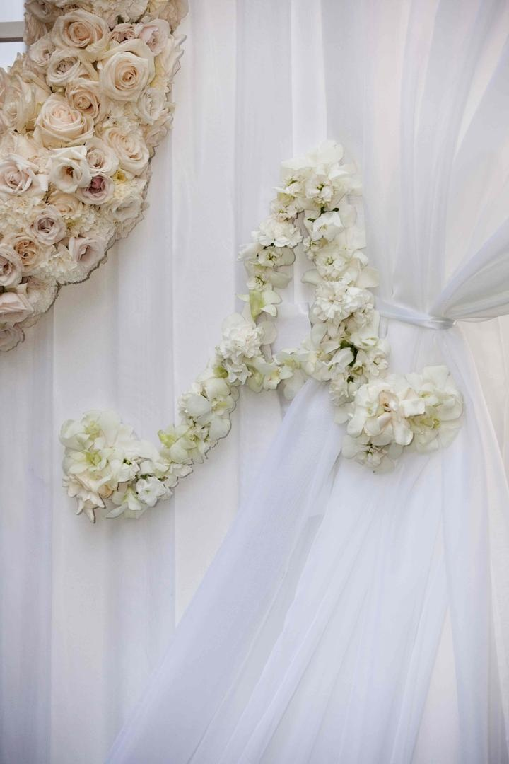 White ceremony drapes tied with flower initial
