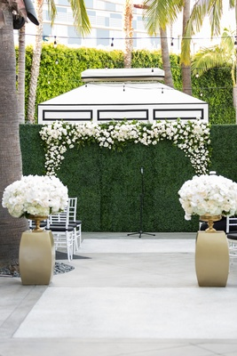 Hedge wall with flowers framing ceremony backdrop
