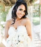 bride with hair half up holding a bouquet of ivory peonies