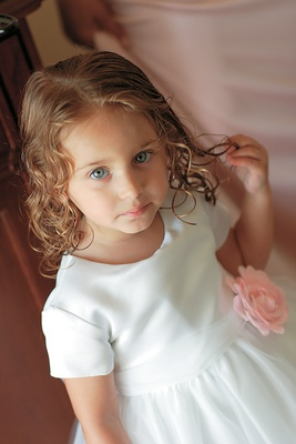 Young flower girl with curls wearing white flower girl dress