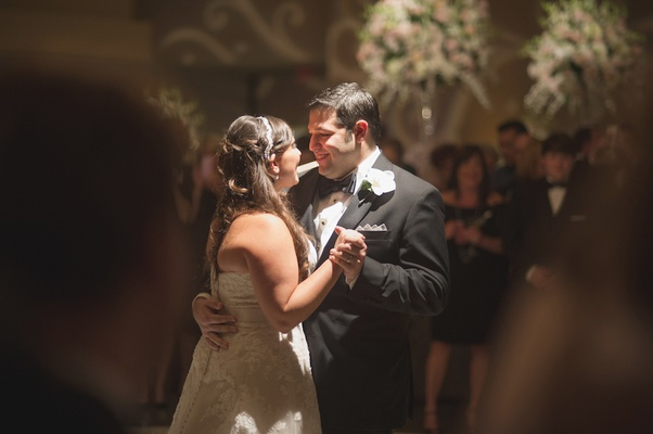 Bride in a strapless Watters lace dress, with off-white sash dances with groom in black tuxedo