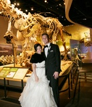 bride in lazaro ball gown, black fur shrug, groom in tuxedo, dinosaur fossils, museum wedding