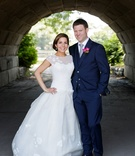 Bride in cap sleeve drop waist wedding dress with groom in navy blue suit and tie