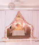 curtain parted and lined with pink and white flowers separating rooms of wedding reception