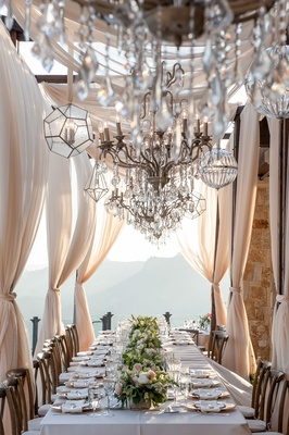 Wedding reception at Malibu rocky oaks vineyard estate long king's table with flower runner drapery