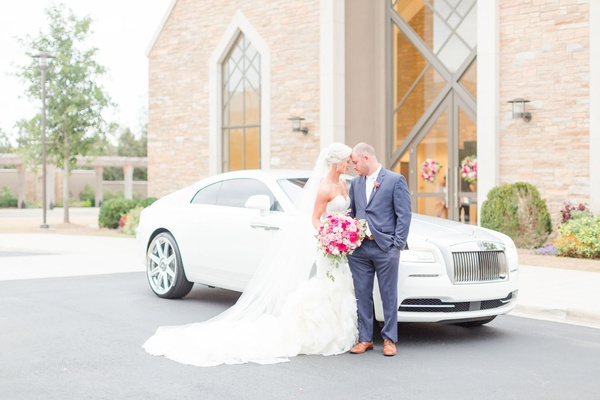 bride and groom in front of bentley getaway car church ceremony to reception transportation
