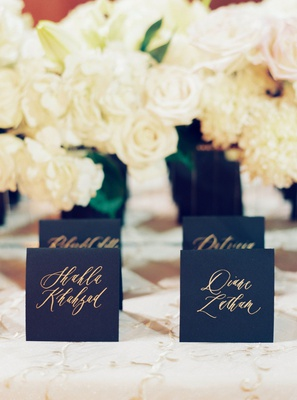 wedding reception escort cards black stationery card stock with gold calligraphy white rose flowers