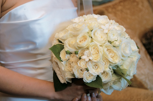 Bride holds white and cream flowers